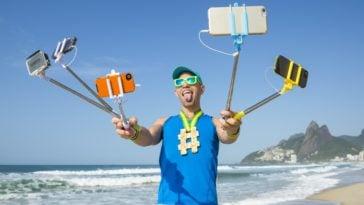 A man taking selfie using various gadgets on selfie sticks.